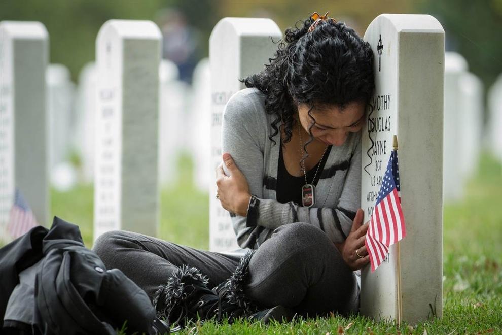 Thania Sayne se penche sur la tombe de son mari, qui a été tué en Afghanistan en 2011, au cimetière national d'Arlington.