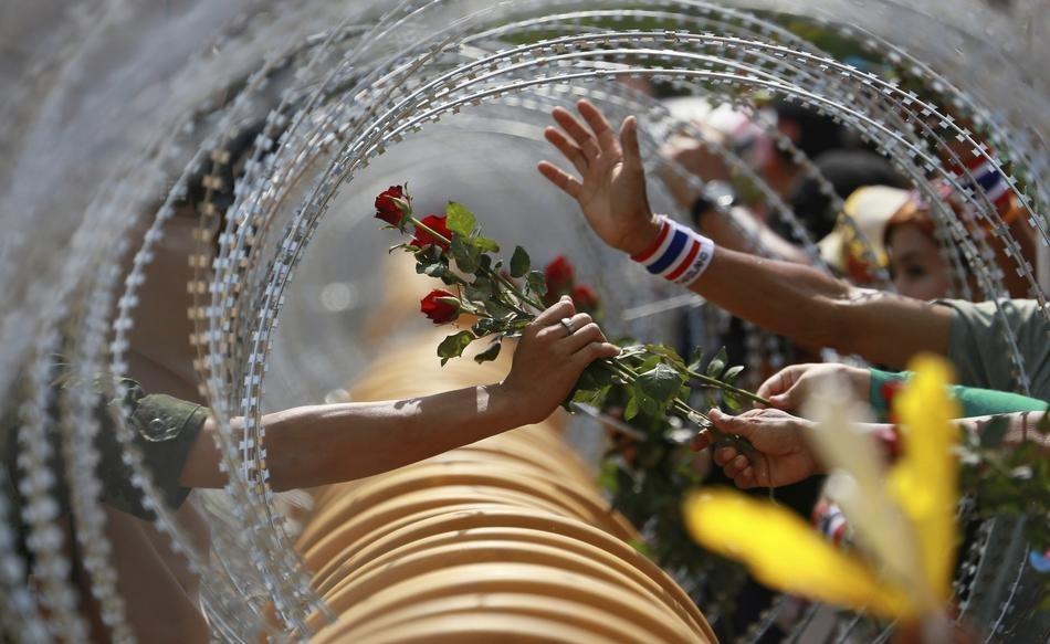 Un manifestant anti-gouvernement donne une rose à un soldat thaïlandais au ministère de la Défense lors d'un rassemblement à Bangkok.