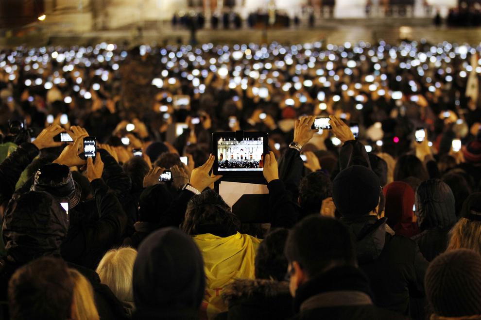 Des Catholiques prennent des photos avec leurs téléphones et tablettes du pape François nouvellement élu et présent sur le balcon de la basilique Saint-Pierre au Vatican.